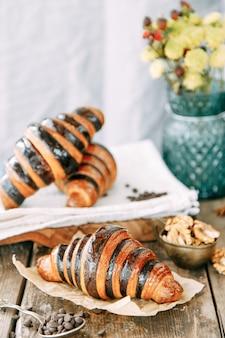 카라멜 유약 클로즈업에 초콜릿 크로와상입니다. 나무 테이블에 디저트의 구성입니다.