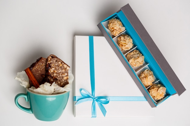 Chocolate in cup and boxes on white