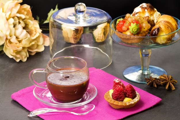 Chocolate cup with fancy cakes and floral decorations