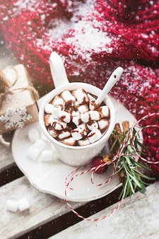 Chocolate cup with marshmallows and christmas decorations seen from above