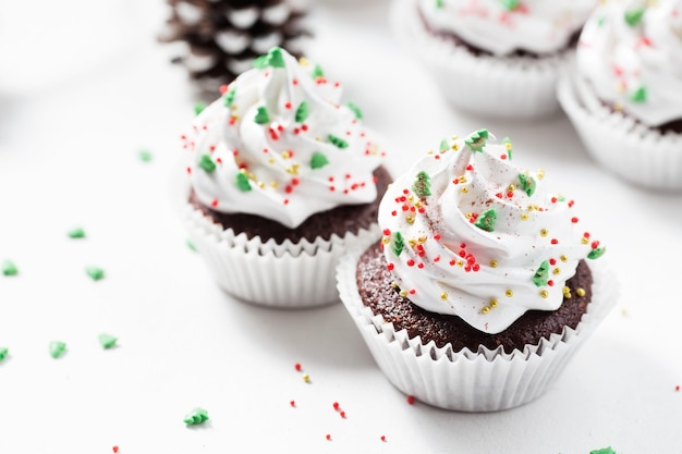 Chocolate cupcake decorated white cream and fir trees.