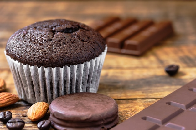 Chocolate cupcake with almond chocolate pieces on wooden floor homemade dessert bakery concept