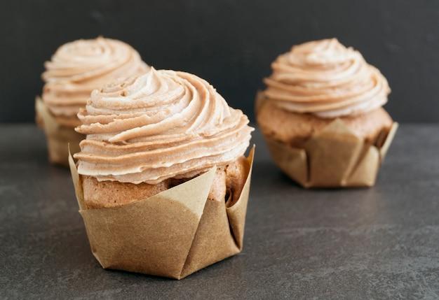 Chocolate cupcake with chocolate cream on black background.