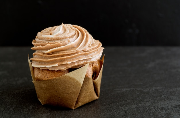 Chocolate cupcake with chocolate cream on a dark background.