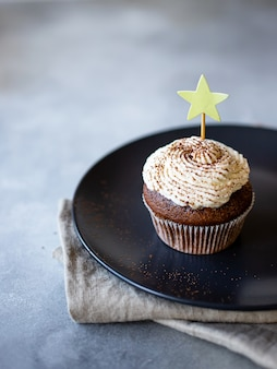 Chocolate cupcake with cream sprinkled with cocoa powder on a dark plate. light gray background. vertical image.