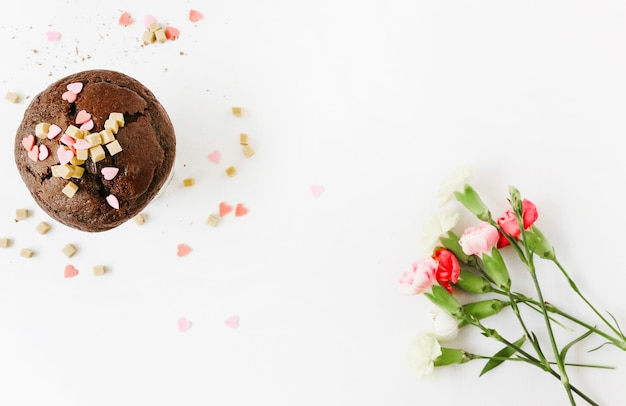 Chocolate cupcake with flowers on white background