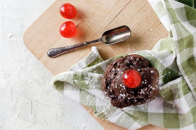 Шоколадный кекс с глазурью на салфетке на деревянной доске и старой ложке