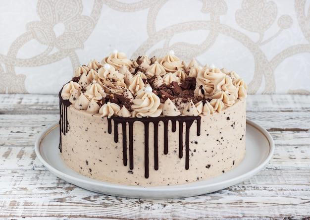 グランジ白い木製の背景にムースクリームのアイシングとチョコレートケーキ