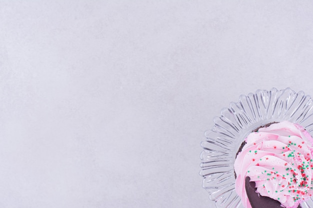 Шоколадный кекс с розовым кремом сверху.