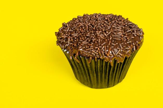노란색 배경이 있는 스프링클이 있는 초콜릿 컵케이크