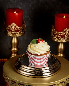 バニラクリームとクリスマスの装飾が施されたチョコレートカップケーキ