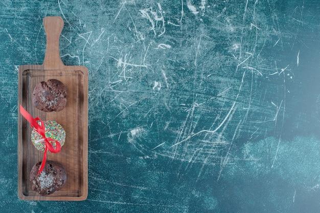 초콜릿 컵 케이크와 파란색 배경에 보드에 사탕 코팅 된 롤리팝. 고품질 사진