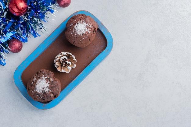 대리석 표면에 화환과 싸구려 옆에 플래터에 초콜릿 컵 케이크와 소나무 콘