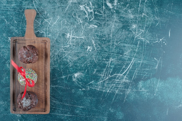 Cupcakes al cioccolato e un lecca-lecca ricoperto di caramelle su una tavola su sfondo blu. foto di alta qualità