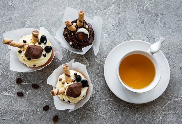 Chocolate cupcakes and cup of tea on concrete background