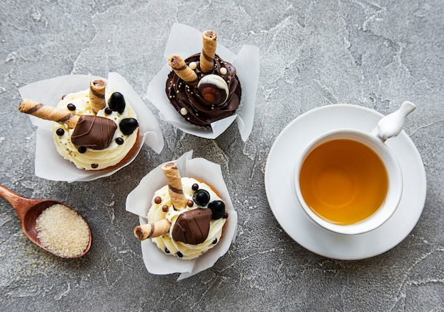 Chocolate cupcakes and cup of tea on concrete table