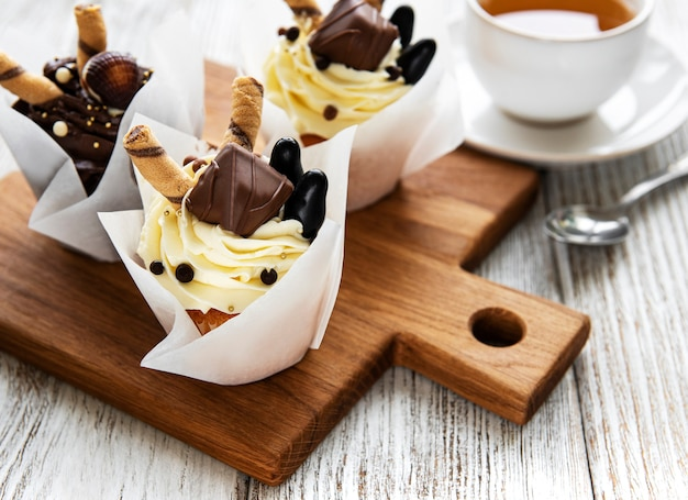 Chocolate cupcakes and cup of tea on white wooden table