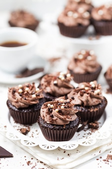 Chocolate cupcakes decorated coffee cheese cream on white plate