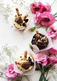 白い大理石の背景にバレンタインデーのチョコレートカップケーキ