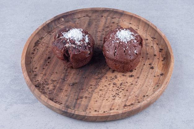 大理石のテーブルの上の木製トレイにチョコレートカップケーキ。