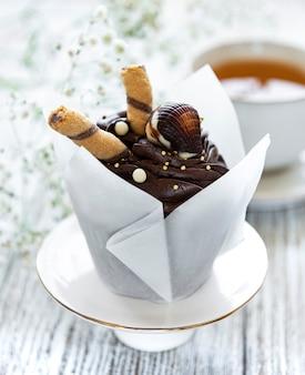 白い木製の背景にチョコレートカップケーキ