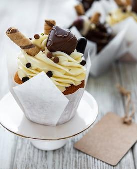 白い木の表面にチョコレートカップケーキ