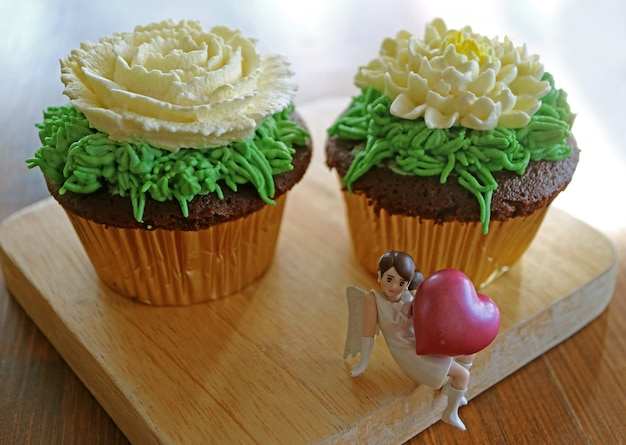 Chocolate cupcakes topped with flower shaped whipped cream with mini angel holding big heart