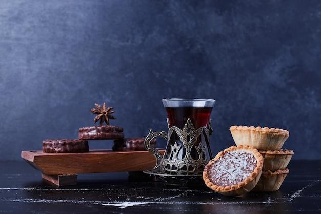 お茶のグラスとチョコレートカップケーキ。