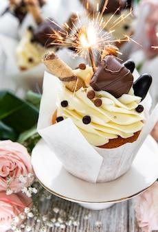 불타는 흰색 나무 바탕에 폭죽과 초콜릿 컵 케이크