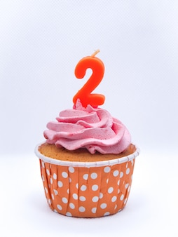 Chocolate cupcakes with candles 2 on white background, birthday or anniversary concept.