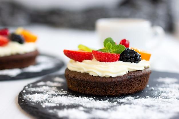 크림치즈 과일과 딸기를 곁들인 초콜릿 컵케이크 커스터드 크림을 곁들인 비스킷 미니 케이크