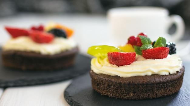 クリームチーズのフルーツとベリーのチョコレートカップケーキ健康的なコーヒーデザートとしてのミニケーキ
