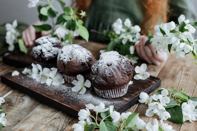 Chocolate cupcakes on a wooden board among apple blossoms.