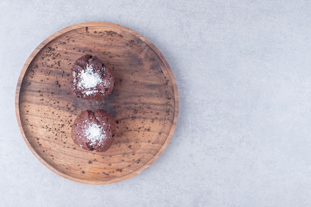 Chocolate cupcakes on a wooden tray on marble