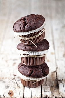 Chocolate dark muffins on rustic wooden table.