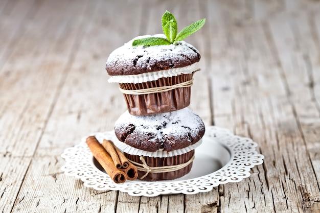Chocolate dark muffins with sugar powder, cinnamon sticks and mint leaf on white plate