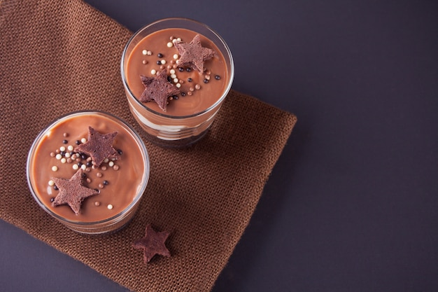 Chocolate dessert in glass jars on a table with wooden spoon. top view.