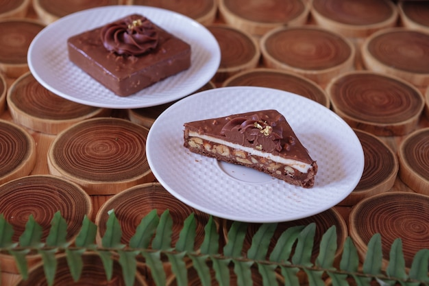 Chocolate dessert with filling of caramel nuts and nougats the cake is covered with chocolate on a w...