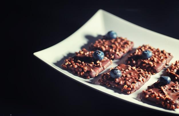 견과류와 신선한 딸기를 곁들인 초콜릿 디저트. 유약에 든 커피 비스킷과 과일을 곁들인 견과류 부스러기를 위한 달콤한 간식.