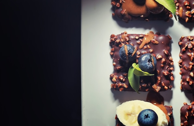 Chocolate dessert with nuts and fresh berries. sweet snack for coffee biscuit in glaze and nut crumbs with fruit.