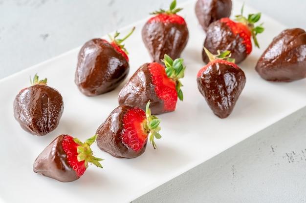 흰색 서빙 접시에 초콜릿 담근 딸기