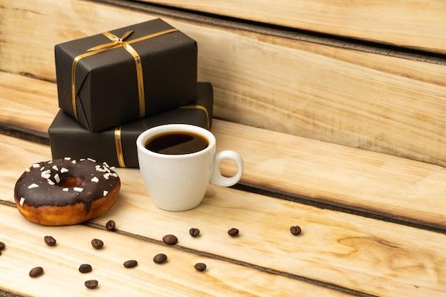 초콜릿 도넛, 커피 한잔과 나무 테이블에 검은 포장에 선물.