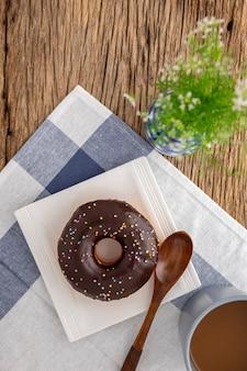ナプキンのコーヒーと花瓶の横にある白い正方形のセラミックプレートにチョコレートドーナツと木のスプーン
