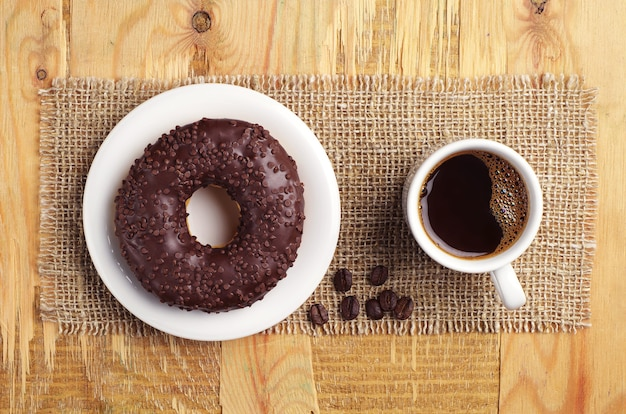 Chocolate donut and coffee on old wooden background