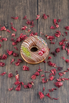 Chocolate donut and dried rose petals on wooden surface.