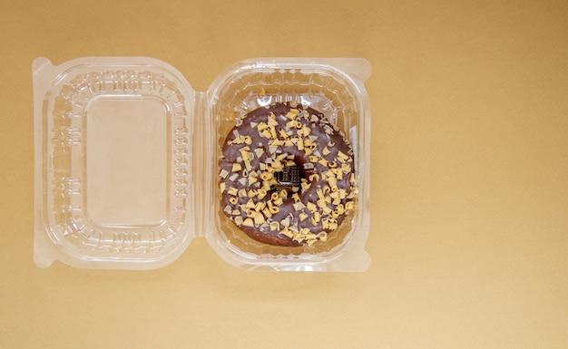 갈색 또는 커피 배경에 플라스틱 용기에 초콜릿 도넛. 테이크 아웃 아침 식사 개념입니다. 도넛 1개는 플라스틱 상자에 포장되어 배송됩니다. 집으로 배달되는 달콤한 페이스트리. 평면도.