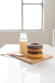 チョコレートドーナツ。自宅のリビングルームのテーブルにミルクと朝の朝食。