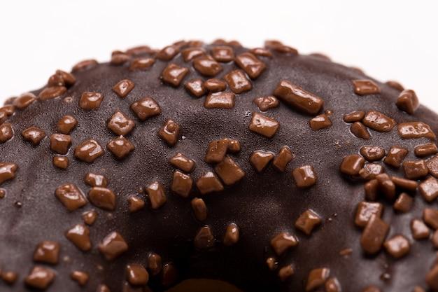 Шоколадный пончик на белом фоне крупным планом.
