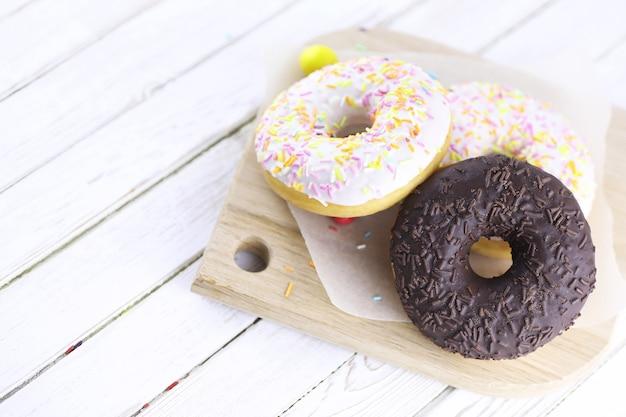 나무 흰색 배경에 초콜릿 도넛과 달콤한 장식품이 흩어져 있습니다.