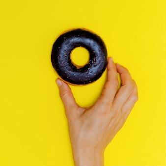 노란색 배경에 초콜릿 도넛입니다. 플랫 레이 패스트 푸드 아트. 도넛 애호가 개념
